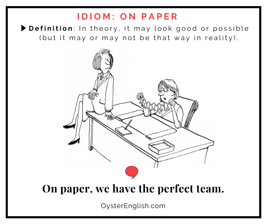 A cartoon businesswoman sits at a desk holding up a chain of connecting paper cutout people. She laments to her colleague: On paper, we have the perfect team. The definition of the idiom