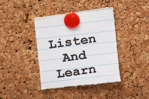 Corkboard with a piece of paper tacked on that has the message: Listen and Learn.